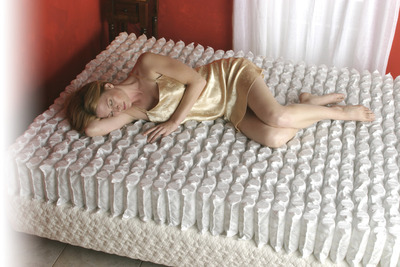A woman rests on top of the Gold Bond Encased Coil series.